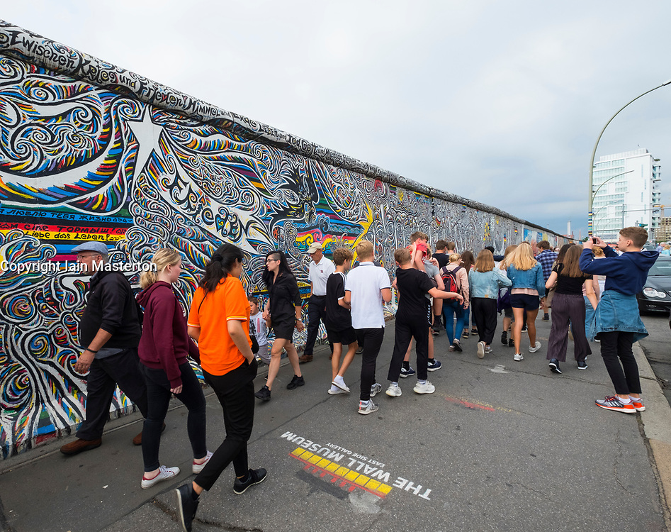 Many tourists walk past mural painted on original section of Berlin Wall at East Side gallery in Berlin, Germany ...Editorial Use Only