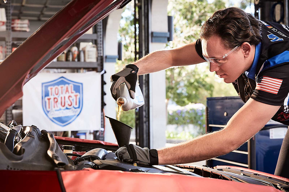 Raymond Rudolph photographs a mechanic performing an oil change during an advertising photoshoot for Speedee-Midas.