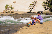 Mother and daughter watching cascade from the banks of the Tuolumne River, Tuolumne Meadows, Yosemite National Park, California