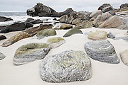 Smooth granite boulders on a sandy beach on Vaeroy Island, Lofoten Islands, Norway.
