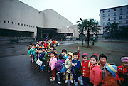 Chinese school children line up to view the Zigong Dinosaur Museum erected over the Dashanpu Quarry, filled with dinosaurs from the mid-Jurassic.
