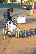 a man with a bicycle selling candied peanuts and hot water for mate herbal tea, garraninada mani calientes. Street merchant, stall. Montevideo, Uruguay, South America