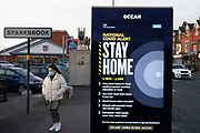 National Covid Alert sign for people to stay at home while the second national lockdown continues with just a week before the new three tier system begins, people wearing face masks out and about in Sparkhill on the border with Sparkbrook as all non-essential shops are closed on 24th November 2020 in Birmingham, United Kingdom. The national lockdown is a huge blow to the economy and for individual businesses who were already struggling with only offering limited services.