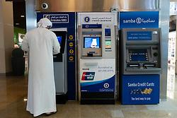 Emirati man using cash ATM machine in Dubai, UAE