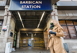 © Licensed to London News Pictures. 19/03/2020. London, UK. A woman walks past Barbican tube station near St Bartholomew's Hospital in London which is seen closed this morning. Transport for London (TfL) are closing a number of underground stations from today, as partial closure of the tube and rail network begins in response to the growing coronavirus outbreak in the captial. Photo credit: Vickie Flores/LNP
