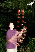 Boy juggling three balls.