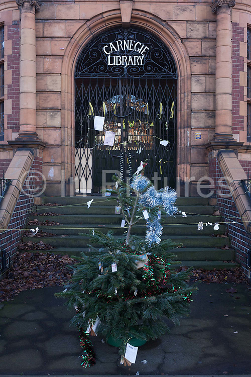 A Christmas tree standing alone outside the now empty Carnegie Library, on 2nd January 2017, in the London borough of Lambeth, England. Shut by Lambeth council and occupied by protesters for 10 days in April, the library which was bequeathed by American philanthropist, Andrew Carnegie has been locked ever since because, say Lambeth austerity cuts are necessary even though 24hr security make it more expensive to keep closed than open for the local community. A gym that locals say they dont want or need is planned to replace the working library and while some of the 20,000 books on shelves will remain, no librarians will be present to administer it.