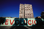 """Revolucion"" painted on a wall surrounding some crumbling buildings in Havana, Cuba."