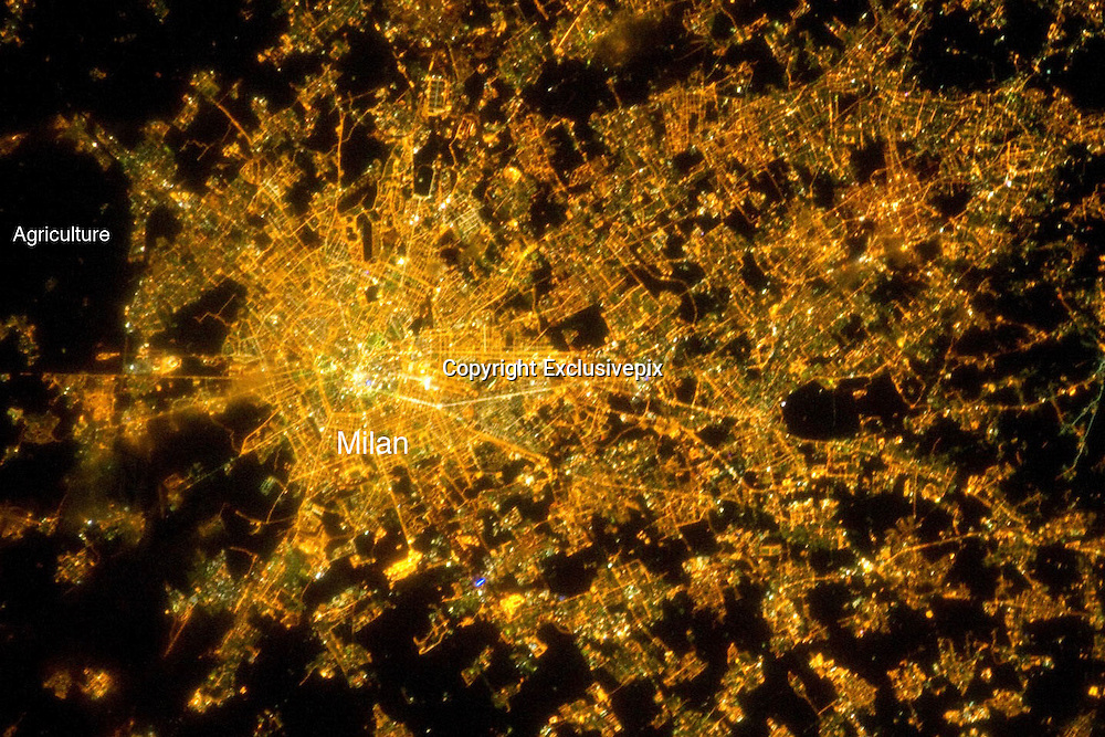 City's By Night<br /> <br /> Milan at Night<br /> <br /> The metropolitan area of Milan (or Milano) illuminates the Italian region of Lombardy in a pattern evocative of a patchwork quilt. The city of Milan forms a dense cluster of lights in this astronaut photograph, with brilliant white lights indicating the historic center of the city where the Duomo di Milano (Milan Cathedral) is located.<br /> Large dark regions to the south (image left) contain mostly agricultural fields. To the north, numerous smaller cities are interspersed with agricultural fields, giving way to forested areas as one approaches the Italian Alps (not shown). Low, patchy clouds diffuse the city lights, producing isolated regions that appear blurred. The Milan urban area is located within the Po Valley, a large plain bordered by the Adriatic Sea to the east-southeast, the Italian Alps to the north, and the Ligurian Sea and Appenines Mountains to the south.<br /> ©Earth Observatory/Exclusivepix