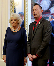 The Duchess of Cornwall, President of the National Osteoporosis Society, is greeted by 'Strictly Come Dancing' judge Craig Revel Horwood as she arrives at Buckingham Palace in London to host a tea dance attended by 'Strictly Come Dancing' dancers and judges to highlight the benefits for older people of staying active.