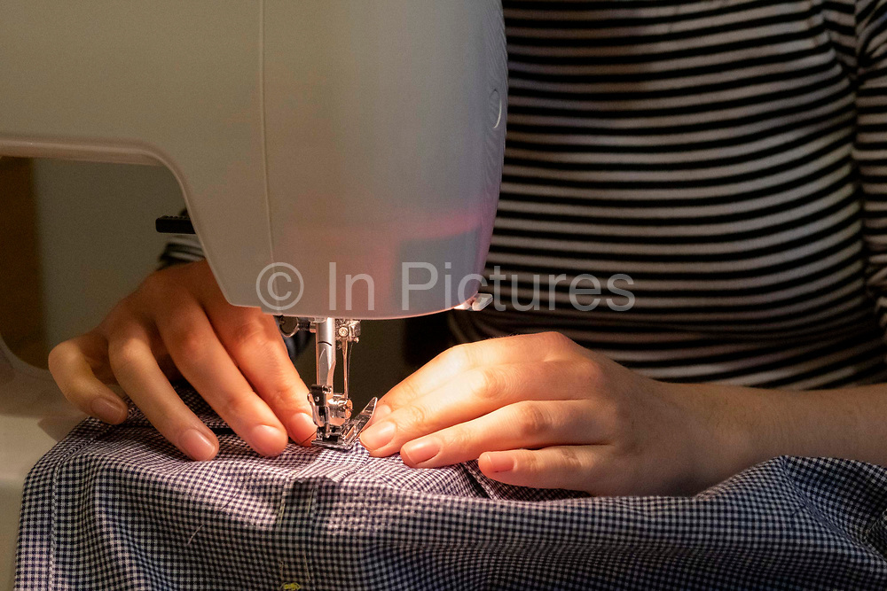 Using her own sewing machine, a young dressmaking hobbyist woman sews together the seams of a home-made dress that shes created from a pattern in her home, on 6th March 2021, in London, England.
