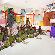 CAPTION: The trainer is teaching the girls about the menstrual cycle, what it means for them, and how they can take care of their needs after it begins. LOCATION: Mahila Samakhya, Ratu (block), Ranchi (city), Jharkhand (state), India. INDIVIDUAL(S) PHOTOGRAPHED: Adult: Rajni Lakra; children: Salomi Horo (standing front), Holika Lakraand (standing back) and multiple other people.