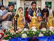 16 APRIL 2014 - BANGKOK, THAILAND:  People bathe Buddha statues set out for Songkran in Hua Lamphong Railway Station, the main train station in Bangkok. Thai highways, trains and buses were packed Wednesday as Thais started returning home after the long Songkran break. Songkran is normally three days long but this year many Thais had at least an extra day off because the holiday started on Sunday, so many Thais started traveling on Friday of last week.    PHOTO BY JACK KURTZ