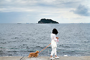 woman walking her dog at Umikaze park, Yokosuka with Tokyo Bay and Sarushima Island