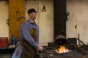 Blacksmith Frank Verga working on a forge in a metal working shop in Charleston, SC