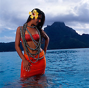 A model draped with approximately $5 million dollars of black pearls in the lagoon of Bora Bora.