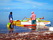 Locals prepare a pumpboat moored along the shore on calm ocean waters, Bohol Island, Philippines, Southeast Asia