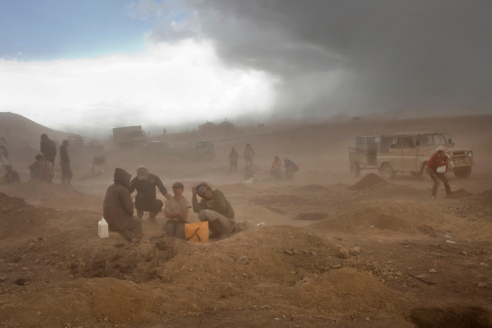 This new mineral wealth comes with a price. Environmental activists say mining has caused 850 rivers and more than 1,000 lakes to go dry. Here ninja miners attempt to shelter from the dust storm kicked up by high winds and the exposed dirt from their gold mining operations.