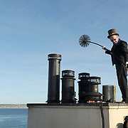 Chimney sweep Jerry Forbes works atop the roof of the Spindrift Inn on Cannery Row in Monterey, Calif. in February 2012.