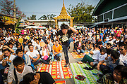 """15 MARCH 2014 - NAKHON CHAI SI, NAKHON PATHOM, THAILAND: A man jumps into the air to rush the stage as he goes into a trance state at the Wat Bang Phra tattoo festival. Wat Bang Phra is the best known """"Sak Yant"""" tattoo temple in Thailand. It's located in Nakhon Pathom province, about 40 miles from Bangkok. The tattoos are given with hollow stainless steel needles and are thought to possess magical powers of protection. The tattoos, which are given by Buddhist monks, are popular with soldiers, policeman and gangsters, people who generally live in harm's way. The tattoo must be activated to remain powerful and the annual Wai Khru Ceremony (tattoo festival) at the temple draws thousands of devotees who come to the temple to activate or renew the tattoos. People go into trance like states and then assume the personality of their tattoo, so people with tiger tattoos assume the personality of a tiger, people with monkey tattoos take on the personality of a monkey and so on. In recent years the tattoo festival has become popular with tourists who make the trip to Nakorn Pathom province to see a side of """"exotic"""" Thailand.   PHOTO BY JACK KURTZ"""
