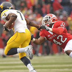 Dec 5, 2009; Piscataway, NJ, USA; West Virginia running back Noel Devine (7) straight-arms Rutgers linebacker Steve Beauharnais (42) during first half NCAA Big East college football action between Rutgers and West Virginia at Rutgers Stadium.