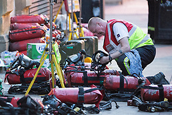 © Licensed to London News Pictures . 13/07/2013 . Manchester , UK . Fire fighters check through breathing apparatus a block away from the fire . A fire fighter is dead and two 15 year old girls are under arrest on suspicion of manslaughter after a blaze in Manchester yesterday (Saturday 13th July) . More than 60 fire fighters tackled a blaze at Paul's Hair World on Oldham Street in Manchester City Centre late in to the night (Saturday 13th July 2013) . Twelve crews from four stations were deployed . Several streets in a block in the city centre are sealed off . Photo credit : Joel Goodman/LNP