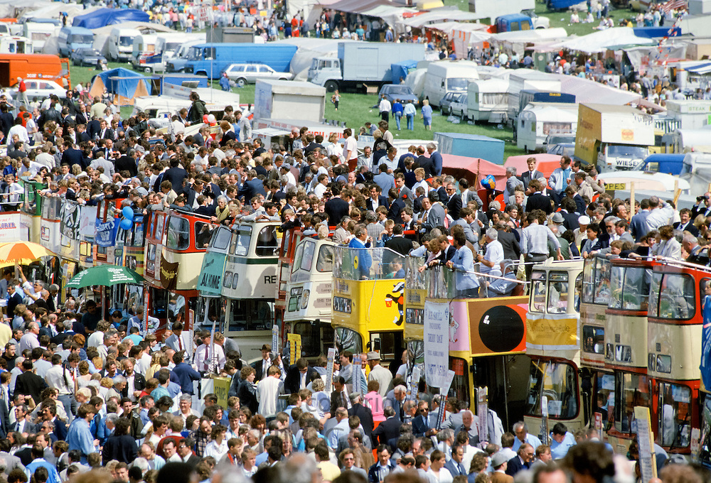 Crowds of spectactors on traditional open-topped buses in The Hill public area at Epsom Racecourse for Derby Day, UK