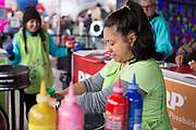 AARP's Misty Bahr sets up paint for the spin art bikes at the AARP Block Party at the Albuquerque International Balloon Fiesta in Albuquerque New Mexico USA on Oct. 7th, 2018.
