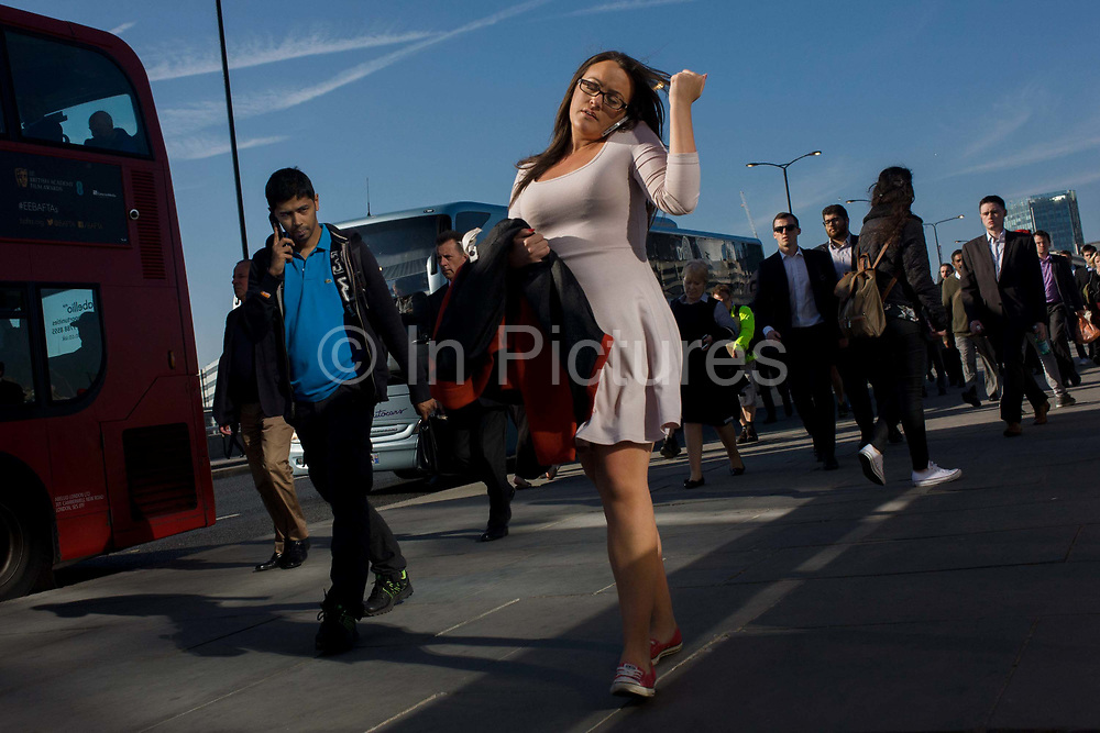 Londoners cross southbound over London Bridge during the evening rush hour. As a young woman fiddles with her long hair while talking on her phone that she has lodged in her shoulder, a young man alongside her glances sideways. Commuters stride nearby others walking out of the City of London. There has been a crossing over the Thames here since the Romans first forded the river in the early 1st Century with subsequent medieval and Victorian stone bridges becoming an important thoroughfare from the City on the north bank, to Southwark on the south where transport hubs such as the mainline station gets commuters to the suburbs and satellite towns.