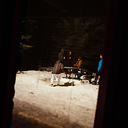 Joseph Paine passes a beer to a spectator during Hostel X team practice in a window reflection.