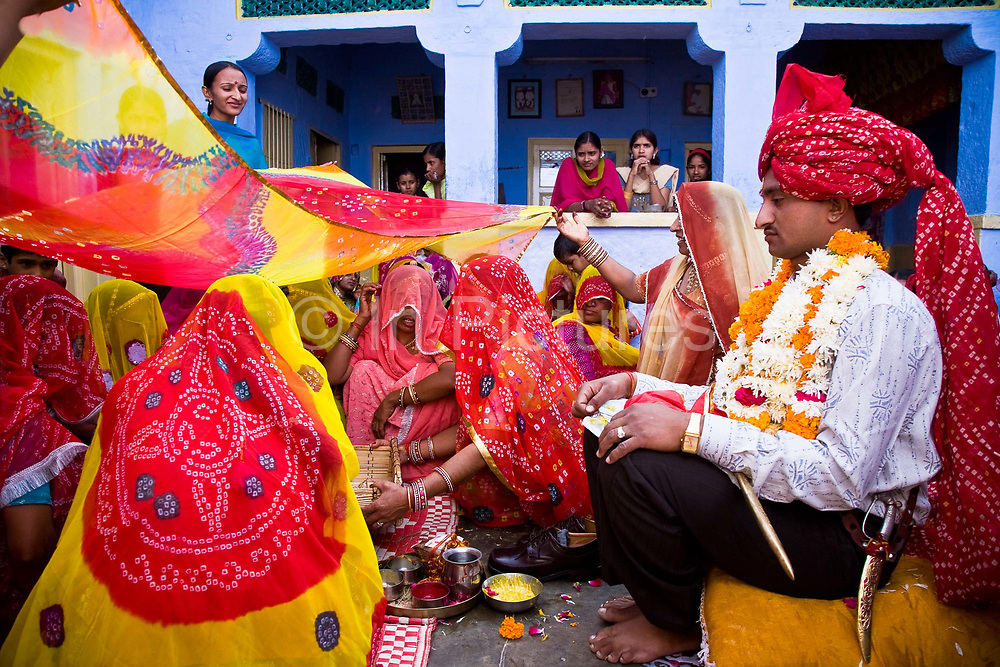 A groom dressed in turban and festooned in a large garland of flowers is surrounded by women from his village as he sits patiently for the wedding ceremony  to begin, Salawas, Rajasthan, India.