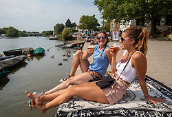 © Licensed to London News Pictures. 08/08/2020. London, UK. Friends Anne Carneigie (left) from Chiswick and Siagosia Horne from Wandsworth enjoy a cooling drink next to the River Thames at Richmond in South West London as temperatures reach to 35c for the second day in a row. Thousands of sun seekers have flocked to parks, rivers and the south coast as temperatures soar with beaches and roads becoming jammed with holidaymakers. The heat is set to continue for the rest of the week with temperatures expected reach over 30C. Photo credit: Alex Lentati/LNP