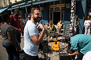 Busker with a guitar stops for a laugh on Portobello Road Market in Notting Hill, West London, England, United Kingdom. People enjoying a sunny day out hanging out at the famous Sunday market, when the antique stalls line the street.  Portobello Market is the worlds largest antiques market with over 1,000 dealers selling every kind of antique and collectible. Visitors flock from all over the world to walk along one of Londons best loved streets.