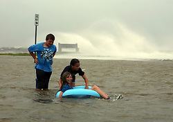 28 August 2012. New Orleans, Louisiana,  USA. <br /> Children play in flood water as Lake Pontchartrain crashes against the sea wall. Hurricane Isaac spins in the Gulf just waiting to come ashore. The 7th year anniversary of Hurricane Katrina is tomorrow and with a storm lurking in the Gulf many in the city are on edge.<br /> Photo; Charlie Varley