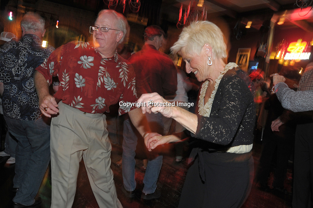 Jim Neblett, 64, left, and Gail Neblett, 64, enjoy the late night dance scene at the Bourban St. bar in the main downtown square of The Villages, Fla., Saturday, Jan. 17, 2009. (Photo by Phelan M. Ebenhack)