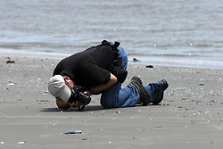 13 May 2010. Elmer Island, Lafourche Parish, Louisiana. <br /> Ted Jackson of the New Orleans Times Picayune on the beach as oil starts arriving on the baches from the Deepwater Horizon catastrophe on the beaches. <br /> Photo credit; Charlie Varley/varleypix.com