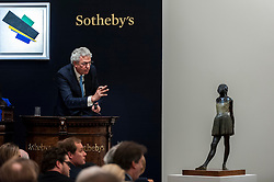"© Licensed to London News Pictures. 24/06/2015. London, UK. The Sotheby's auctioneer manages bids for Edgar Degas' ""Petite danseuse de quartorze ans"" which sold for a hammer price of £14m, £2m more than its estimate of £12m. Sotheby's Impressionist & Modern art evening sale realised a total of £178.6m, the second highest total for any sale ever held in London. Photo credit : Stephen Chung/LNP"
