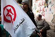 A man with a flag and others who have been protesting in Tahrir Square come and rest at the Zahrat al-Bustan cafe, Cairo, Egypt