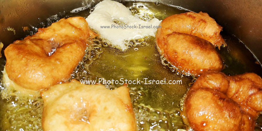 Closeup of home made Doughnuts deep fried in oil in a frying pan
