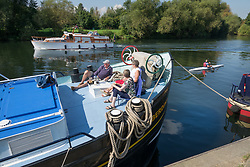 © Licensed to London News Pictures. 02/09/2017. Hampton Court, UK. People enjoy a cup of tea on the deck of their boat moored on the River Thames near Hampton Court. A period of warmer weather is predicted over the next few days after the recent wet spell. Photo credit: Peter Macdiarmid/LNP