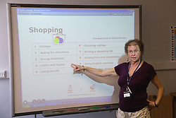 Teacher giving lesson on independent living at a special school using an interactive whiteboard,