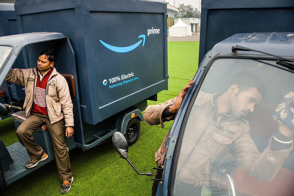 """NEW DELHI, INDIA – JANUARY 13, 2020: The Amazon India team and its partners prepare a fleet of fully electric """"EV"""" rickshaws for debut through social media channels. As part of Amazon's leading effort to mitigate climate change globally, the new fully electric, zero-carbon rickshaws will be deployed throughout India for use in Amazon delivery. The deployment comes in stride with the company's announcement of an additional US $10 billion investment in India – one of the company's fastest-growing markets. """"The 21st Century is going to be an Indian century,"""" Bezos said during his tour of the country, touting the country's dynamism, energy and commitment to democracy as indicators of future growth."""