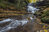 Laurel Creek, a tributary of West Virginia's Gauley River, cascades down layers of rock adorned with autumn leaves of yellow.