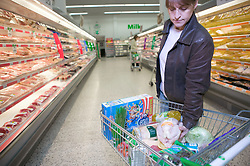 Woman filling her trolley with groceries in a supermarket,
