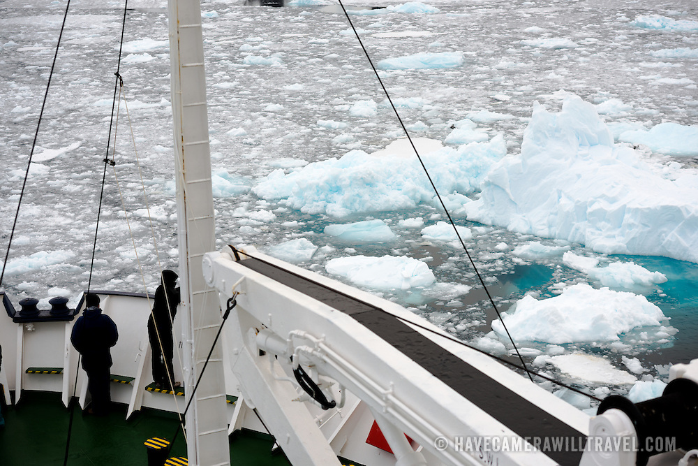 """Passengers stand on the bow of an ice-strengthened cruise ship as it navigates the Lemaire Channel with the surface of the water covered with sheet ice and brash ice. The Lemaire Channel is sometimes referred to as """"Kodak Gap"""" in a nod to its famously scenic views."""