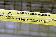 Nederland, Ooij, 2-9-2016 Op het dak van een oude boerenschuur, liggen platen asbest als dakbedekking . Ze worden er door een gespecialiseerd sloop bedrijf vanaf gehaald. Het grote aantel daken van met name boerderijen en schuren vormt op de lange termijn een gezondheidsrisico en moeten allemaal verwijderd worden . Een lint, waarschuwingslint, afzetlintFoto: Flip Franssen