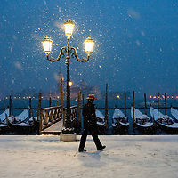 VENICE, ITALY - DECEMBER 17:  Gondolier walks in the snow in San Marco on December 17, 2010 in Venice, Italy. Snow has fallen across much of Europe today and is expected to continue over the weekend, causing traffic chaos and disrupting Christmas deliveries. The gondola is a traditional, flat-bottomed Venetian rowing boat, well suited to the conditions of the Venetian lagoon.