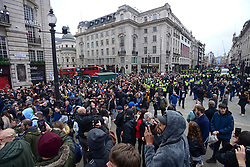 © Licensed to London News Pictures. 20/03/2021. London, UK. Police officers attempt to block protesters on Piccadilly, during a Rally for Freedom in central London, to protest against the continued lockdown restrictions imposed to fight the spread of coronavirus. Similar events are taking place at cities around the world. Photo credit: Ben Cawthra/LNP