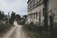 """A dirt road runs past an old, abandoned building in Shushi, Nagorno-Karabakh. A plaque in front of the building states that it is """"The Zhamharyans House and City Hospital (1852)"""". In the early 20th century, Shushi (Shusha in Azeri) was a more populated city than it is today. <br /> <br /> The city contained a mixed Armenian–Azerbaijani population until about a century ago. Following a massacre in 1920 by Azerbaijani forces and their Turkish supporters, the Armenian half of the city's population was mostly killed or expelled. When Armenians captured the city during the Nagorno-Karabakh War in 1992, the Azerbaijinis were driven out. Today, Shushi is almost exclusively Armenian.<br /> <br /> (September 23, 2016)"""