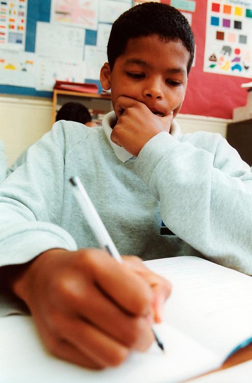 Boy writing in class, Selhurst school for Boys;Croydon;London